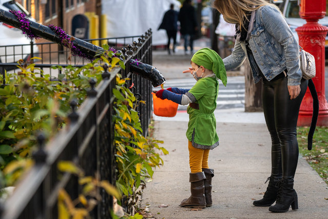 Children receive treats by candy chutes while trick-or-treating for Halloween in Woodlawn Heights on October 31, 2020 in New York City. The CDC shared on their website alternative ways to still celebrate the holiday while being safe. (Photo by David Dee Delgado/Getty Images)