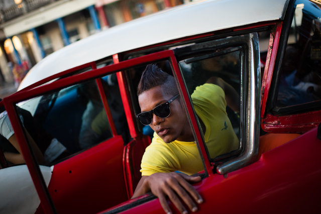 As the sun rises in Havana, one area, La Virgen del Camino, is bustling with morning commuting traffic. Lediel Escobar, 18, is pictured getting out of a shared taxi on April 1, 2015. New roads were constructed in the 1950s in this area. (Photo by Sarah L. Voisin/The Washington Post)