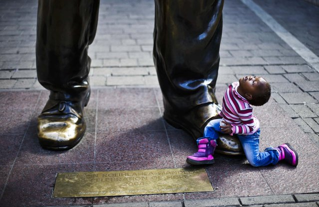 A child looks sits on the shoes of a sculpture of former South African President Nelson Mandela at Nelson Mandela Square in Johannesburg, South Africa, on July 9, 2013. No official update was made on the status of the ailing 94-year-old Nelson Mandela, who was admitted June 8 to the hospital for a recurring lung infection, though court documents say he is breathing with the help of a respirator. (Photo by Markus Schreiber/Associated Press)