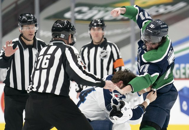 Vancouver Canucks centerZack MacEwen (71) fights with Winnipeg Jets defenseman Derek Forbort (24) during first-period NHL hockey game action in Vancouver, British Columbia, Sunday, February 21, 2021. (Photo by Jonathan Hayward/The Canadian Press via AP Photo)