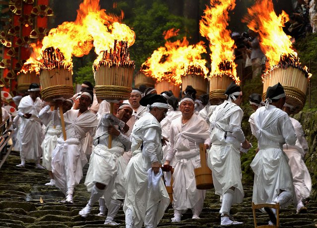 Parishioners carrying giant torches descend a steep stone stairway during the annual grand fire festival of Kumano Nachi Shrine in Nachi Katsuura, western Japan, on July 14, 2013. (Photo by Kyodo News)