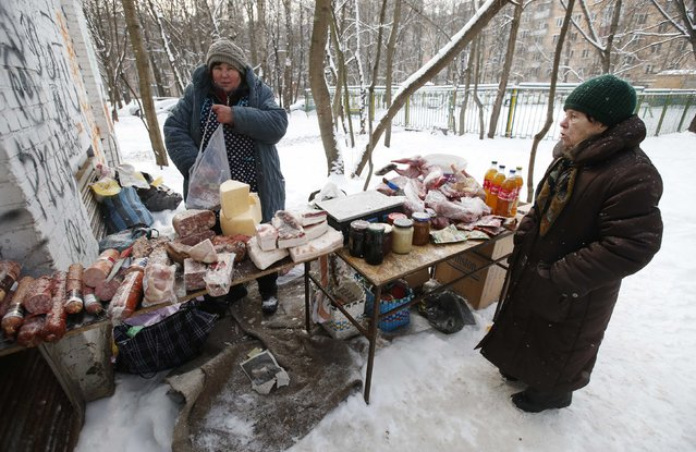 A woman stands near a counter as a street vendor sells food in a yard of an apartment building in Moscow, January 26, 2015. For millions of pensioners who make up about a third of Russia's population, rising prices are spurring anger over declining living standards, threatening a pool of support President Vladimir Putin cannot afford to lose. (Photo by Maxim Zmeyev/Reuters)