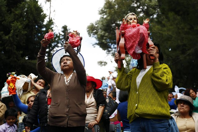 People lift up dressed-up dolls representing baby Jesus during a celebration 40 days after the birth of Jesus in Xochimilco, on the outskirts of Mexico City, February 2, 2015. (Photo by Edgard Garrido/Reuters)