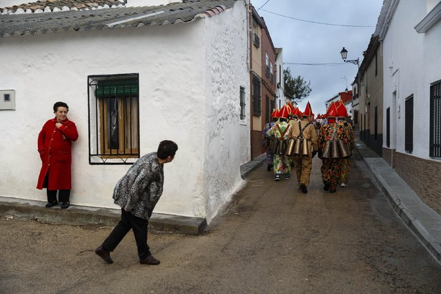"""A woman looks as members of the Endiablada brotherhood march during the 'Endiablada' traditional festival in Almonacid Del Marquesado, Spain, Tuesday, Feb. 3, 2015. The """"Endiablada"""" (The Brotherhood of the Devils) festivals are celebrated each Feb. 2-3 in the central Spanish town of Almonacid del Marquesado since medieval times or before. In the festival, men from the town dress up as devil-type characters in colorful jumpsuit costumes and red miter hats. (AP Photo/Daniel Ochoa de Olza)"""
