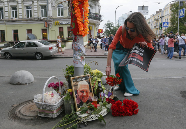 People lay flowers to commemorate late journalist Pavel Sheremet during a rally at the site of his death in Kiev, Ukraine, 20 July 2018. People gathered here in memory of Pavel Sheremet and to stress their demand for an investigation of his killing. Belarus-born Russian journalist Pavel Sheremet was killed in a car explosion in the center of the Ukrainian capital 20 July 2016. (Photo by Sergey Dolzhenko/EPA/EFE)