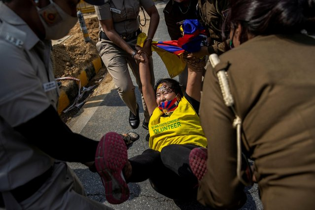 Police officers detain a Tibetan during a protest held to mark the 62nd anniversary of the Tibetan uprising against Chinese rule, outside the Chinese Embassy in New Delhi, India on March 10, 2021. (Photo by Danish Siddiqui/Reuters)