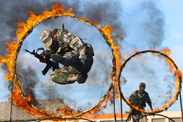 A soldier from the People's Liberation Army jumps through a ring of fire as part of training during the PLA Army Day in Wenzhou, Zhejiang province, on August 1, 2013. (Photo by Reuters)