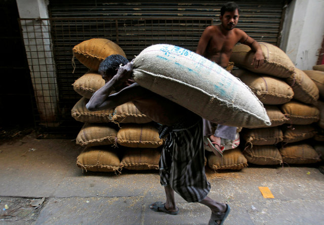 A labourer carries a sack of paddy crops at a wholesale market in Allahabad, India November 17, 2016. (Photo by Jitendra Prakash/Reuters)