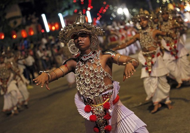 Traditional dancers perform during Navam Perahera, a Buddhist pageant of elephants, dancers and drummers, in Colombo February 2, 2015. Over 50 elephants participated in a street parade for Gangaramaya Temple's annual Perahera festival, along with a nightly procession of dancers, fire twirlers and musicians. (Photo by Dinuka Liyanawatte/Reuters)
