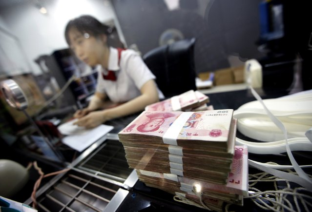 Yuan notes are seen as an employee of the Industrial and Commercial Bank of China Ltd (ICBC) talks to a customer at one of the bank's branch at the Shanghai Free Trade Zone in Pudong district, in Shanghai in this September 24, 2014 file photograph. (Photo by Carlos Barria/Reuters)