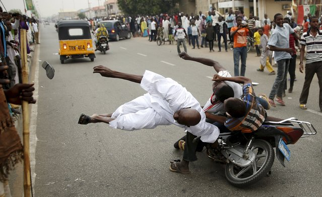 Supporters of the presidential candidate Muhammadu Buhari and his All Progressive Congress hits another supporter with a motorbike during celebrations in Kano, Nigeria March 31, 2015. (Photo by Goran Tomasevic/Reuters)