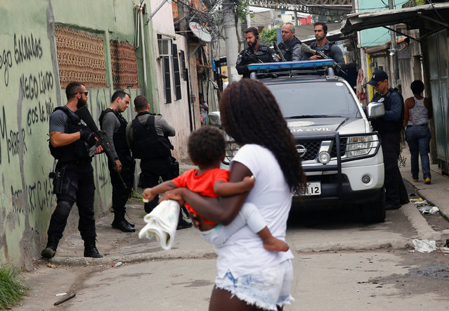 Policemen are pictured near a woman with a baby during an operation against drug dealers in Cidade de Deus or City of God slum in Rio de Janeiro, Brazil, November 23, 2016. (Photo by Ricardo Moraes/Reuters)
