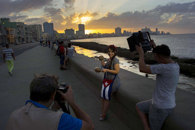 In this December 27, 2015 photo, Estefania Hernandez Perera, 14, who lives in Cuba, is photographed by FotoEcos, a studio that specializes in quinceaneras, along the Malecon in Havana, Cuba. Hernandez is the third in her family to hire FotoEcos for their quinceanera portraits. (Photo by Ramon Espinosa/AP Photo)