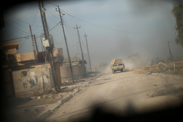 Military vehicles of the Iraqi army take part in an operation against Islamic State militants in the frontline neighbourhood of Intisar, eastern Mosul November 27, 2016. (Photo by Mohammed Salem/Reuters)