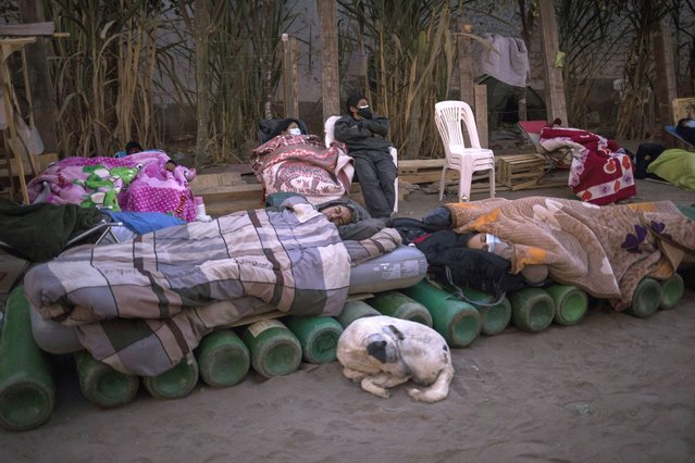 People sleep on top of empty oxygen cylinders, waiting for a shop to open in order to refill their tanks, in the Villa El Salvador neighborhood, as the lack of medical oxygen to treat COVID-19 patients continues in Lima, Peru, Tuesday, April 6, 2021. (Photo by Rodrigo Abd/AP Photo)