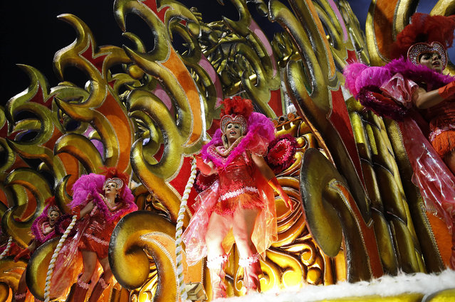 Dancers from the Rosas de Ouro samba school perform on a float during a carnival parade in Sao Paulo, Brazil, Saturday, February 14, 2015. (Photo by Andre Penner/AP Photo)
