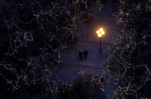 People walk under trees decorated with Christmas lights as the traditional Christmas market opens at the Old Town Square in Prague, Czech Republic, November 26, 2016. (Photo by David W. Cerny/Reuters)