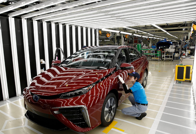 An employee of Toyota Motor Corp. works on the assembly line of Mirai fuel cell vehicle (FCV) at the company's Motomachi plant in Toyota, Aichi prefecture, Japan May 17, 2018. (Photo by Issei Kato/Reuters)
