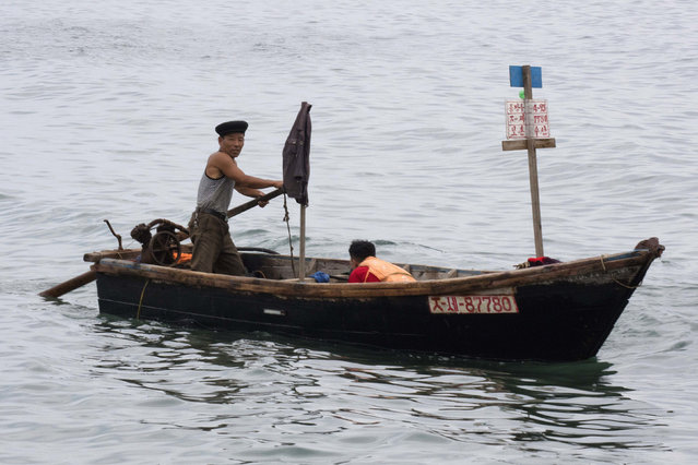 In this August 20, 2018, photo, North Korean fishermen ply the waters off Mount Chilbo, North Korea. (Photo by Ng Han Guan/AP Photo)
