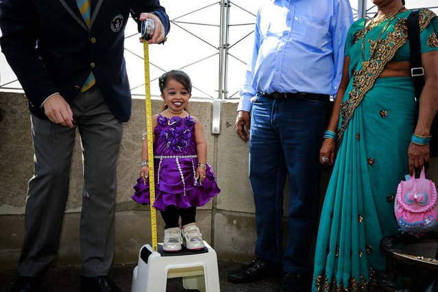 """Jyoti Amge, from Nagpur, India, is measured by a Guinness World Record official on the observation deck of the Empire State Building, on September 12, 2013. Standing 24.7 inches (62.7 cm) tall, Amge has held the title of the """"Shortest Living Woman"""" since her 18th birthday on December 16, 2011. (Photo by Shannon Stapleton/Reuters)"""