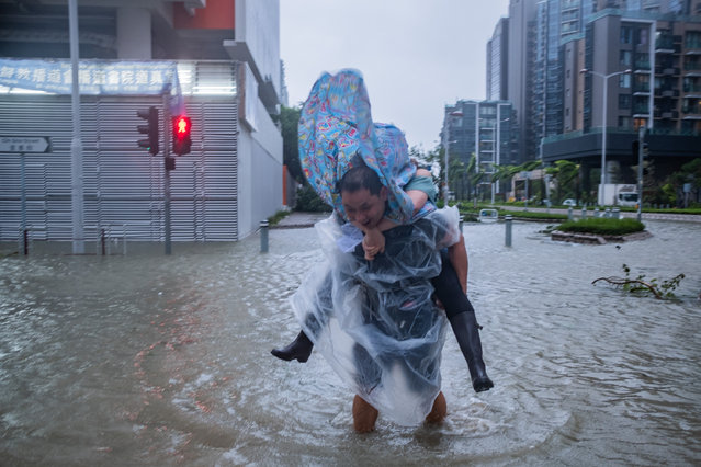 A man carrying a woman cross a flooded road on September 16, 2018 in Hong Kong, Hong Kong. (Photo by Lam Yik Fei/Getty Images)