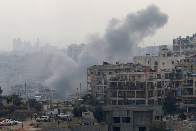 Smoke rises near Pro-Syrian government soldiers after shelling, in al-Izaa area in Aleppo, Syria December 5, 2016. (Photo by Omar Sanadiki/Reuters)