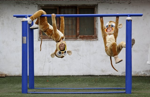 """Children wearing monkey costumes play before a performance of """"Shehuo"""" festival, ahead of Chinese Lunar New Year, in Hancheng, Shaanxi Province, China, January 16, 2016. (Photo by Reuters/Stringer)"""