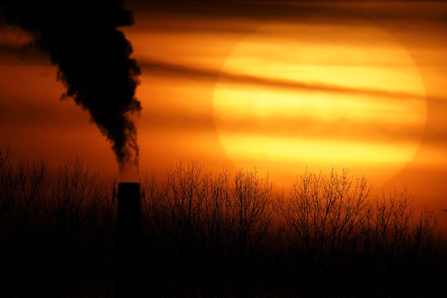 In this Monday, February 1, 2021 file photo, emissions from a coal-fired power plant are silhouetted against the setting sun in Independence, Mo. (Photo by Charlie Riedel/AP Photo/File)