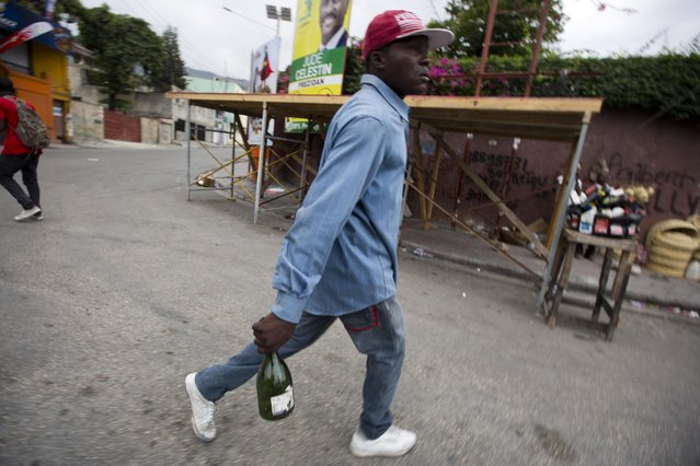 A protester holds a ready to throw empty bottle, during a street protest after it was announced that the runoff Jan. 24, presidential election had been postponed, in Port-au-Prince, Haiti, Friday, January 22, 2016. (Photo by Dieu Nalio Chery/AP Photo)