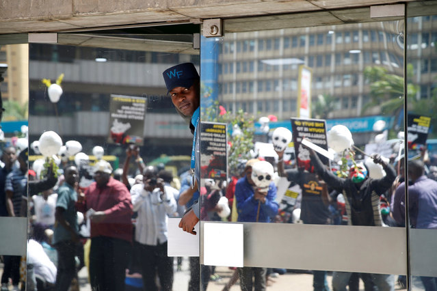 A security guard watches demonstrators during a protest calling the Kenyan government and banks to freeze ill-gotten South Sudanese assets and funds, In front of the KCB bank in Nairobi, Kenya on October 11, 2018. (Photo by Baz Ratner/Reuters)