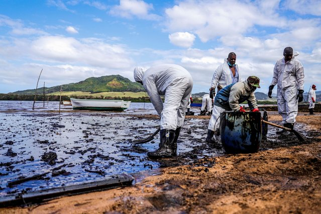 People scoop leaked oil from the vessel MV Wakashio, belonging to a Japanese company but Panamanian-flagged, that ran aground and caused oil leakage near Blue bay Marine Park in southeast Mauritius on August 9, 2020. France on August 8, 2020 dispatched aircraft and technical advisers from Reunion to Mauritius after the prime minister appealed for urgent assistance to contain a worsening oil spill polluting the island nation's famed reefs, lagoons and oceans. Rough seas have hampered efforts to stop fuel leaking from the bulk carrier MV Wakashio, which ran aground two weeks ago, and is staining pristine waters in an ecologically protected marine area off the south-east coast. (Photo by Daren Mauree/AFP Photo)