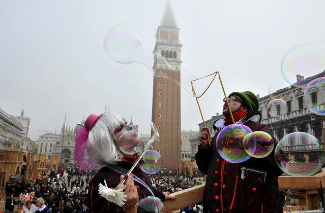 Artists blow bubbles in St. Mark's Square in Venice, Italy, Sunday, January 31, 2016. (Photo by Luigi Costantini/AP Photo)