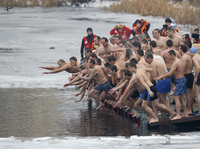 BULGARIA: Men jump into the waters of a lake in an attempt to grab a wooden cross on Epiphany Day in Sofia, Bulgaria January 6, 2016. (Photo by Stoyan Nenov/Reuters)