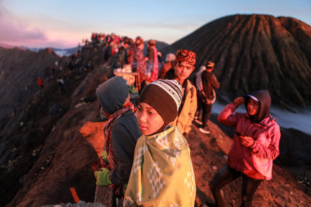 Tenggerese gather during the Yadnya Kasada Festival at crater of Mount Bromo amid the coronavirus pandemic on June 26, 2021. Tenggerese people are a Javanese ethnic group in Eastern Java who claimed to be the descendants of the Majapahit princess. Their population of roughly 500,000 is centered in the Bromo Tengger Semeru National Park in eastern Java. The most popular ceremony is the Kasada festival, which makes it the most visited tourist attraction in Indonesia. The festival is the main festival of the Tenggerese people and lasts about a month. On the fourteenth day, the Tenggerese made a journey to Mount Bromo to make offerings of rice, fruits, vegetables, flowers and livestock to throw them into the volcano's caldera. The origin of the festival lies in the 15th century princess named Roro, the principality of Tengger with her husband Joko Seger, and the childless couple asked mountain Gods for help in bearing children. The legend says the Gods granted them 24 children but on the provision that the 25th must be added to the volcano in sacrifice. The 25th child, Kesuma, was finally sacrificed in this way after an initial refusal, and the tradition of throwing sacrifices into the Caldera to appease the mountain Gods continues today. (Photo by Bayu Novanta/SOPA Images/Rex Features/Shutterstock)