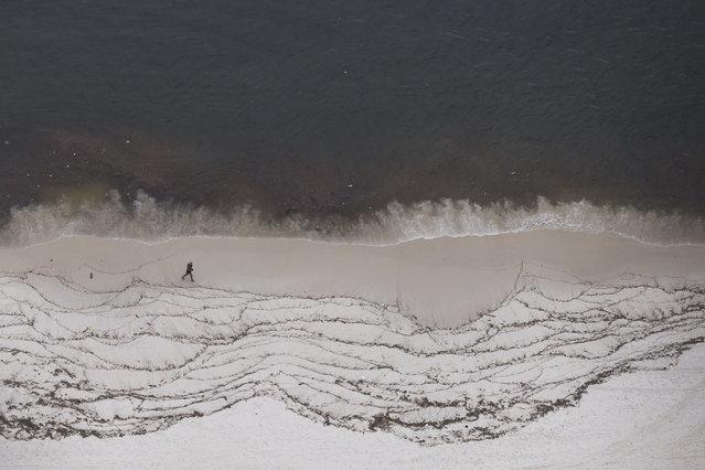 A man walks on the shore of Icarai Beach in Niteroi, across the bay from Rio de Janeiro, Brazil, Monday, March 23, 2015. (Photo by Felipe Dana/AP Photo)