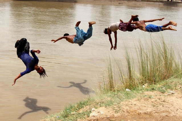 Pakistani boys jump in the water to cool off in a pond to beat the heat wave continues in Larkana, Pakistan, 26 June 2021. Pakistan's Meteorological Department (PMD) said the weather in the city will remain hot and humid for the next three days. (Photo by Waqar Hussain/EPA/EFE)