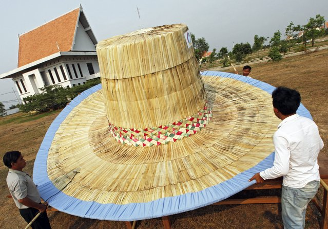 Cambodian craftsmen make a giant hat as they prepare for the upcoming Angkor Sankranta festival in Siem Reap province, Cambodia, 23 March 2015. Cambodia will celebrate Angkor Sangkranta festival as a part of the Khmer New Year celebration, falling from 14 to 16 April. (Photo by Mak Remissa/EPA)