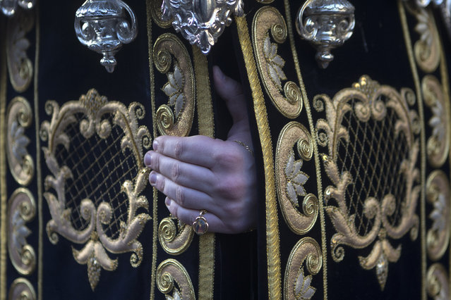 The hand of a penitent from Los Estudiantes brotherhood gets a grip onto a platform that several penitents carry with a statue of the Virgin Mary during a Palm Sunday Holy week procession in Madrid, Spain, Sunday, March 29, 2015. (Photo by Paul White/AP Photo)