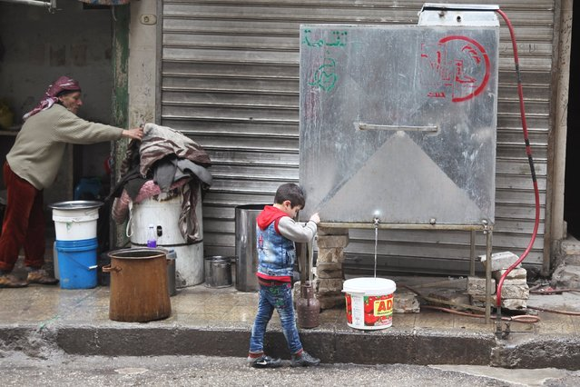 A boy fills containers with water from one of the water tanks that were placed and supervised by the Syrian Arab Red Crescent and other humanitarian organisations in Aleppo, Syria January 22, 2016. (Photo by Abdalrhman Ismail/Reuters)