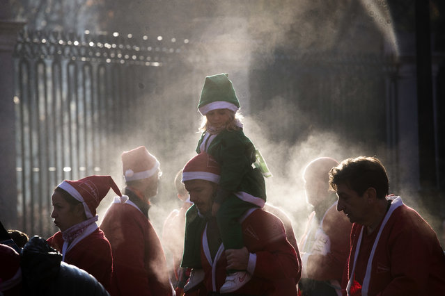 People dressed in Santa Claus costumes arrive at the finish line after taking part in a morning run in Madrid, Sunday, December 9, 2018. Thousands of people ran in the annual Santa race through the streets of the Spanish capital. (Photo by Emilio Morenatti/AP Photo)