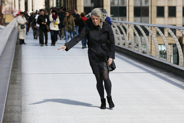 A woman struggles to keep her balance as she crosses the Millennium Bridge during strong winds in London, March 31, 2015. (Photo by Stefan Wermuth/Reuters)