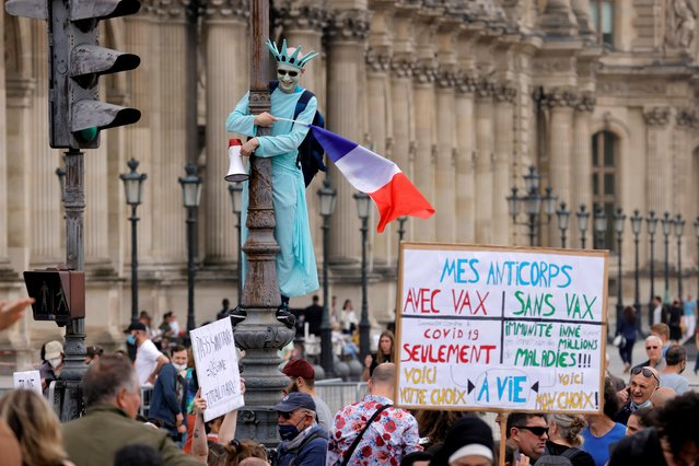A demonstrator dressed as the statue of Liberty takes part in a protest against the new measures announced by French President Emmanuel Macron to fight the coronavirus disease (COVID-19) outbreak, in Paris, France, July 17, 2021. (Photo by Pascal Rossignol/Reuters)
