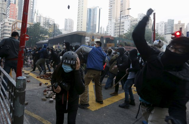Protesters throw bricks as a journalist takes cover during a clash with riot police at Mongkok district in Hong Kong, China February 9, 2016. (Photo by Bobby Yip/Reuters)
