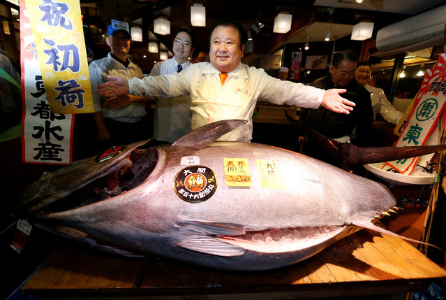 Kiyomura Co's President Kiyoshi Kimura (C), who runs a chain of sushi restaurants Sushi Zanmai, poses with a 212 kg (467 lbs) bluefin tuna at his sushi restaurant outside Tsukiji fish market in Tokyo, Japan, January 5, 2017. Kimura won the bid for the tuna caught off Oma, Aomori prefecture, northern Japan, with a 74 million yen (633,000 USD) at the fish market's first tuna auction this year. (Photo by Issei Kato/Reuters)
