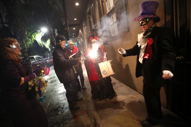 """Members of the """"Societe des Champs Elysee"""" light fireworks on their way to a bar, after riding the Rampart-St. Claude street car line, which just opened last fall, to commemorate the official start of Mardi Gras season, in New Orleans, Friday, January 6, 2017. (Photo by Gerald Herbert/AP Photo)"""