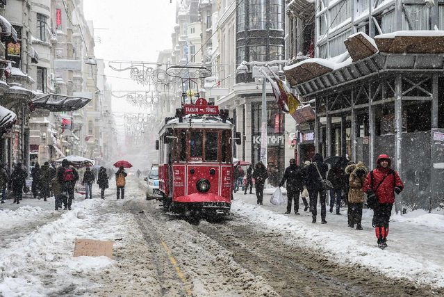 People walk on the Istiklal avenue during snowfalls in Istanbul on January 7, 2017. A heavy snowstorm paralysed life in Istanbul with hundreds of flights cancelled and the Bosphorus closed to shipping traffic. The snowstorm dumped almost 40 centimetres (16 inches) of snow in parts of the Turkish metropolis overnight, causing havoc on roads as travellers sought to leave the city for the weekend getaway. (Photo by Yasin Akgul/AFP Photo)