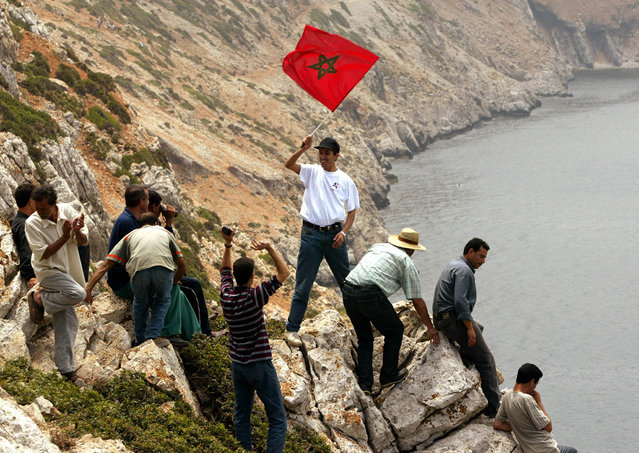 Moroccans cheer on a cliff as a man disembarks carrying a Moroccan flag on the disputed Perejil Islet off Morocco's Mediterranean coast, July 2002. (Photo by Desmond Boylan/Reuters)