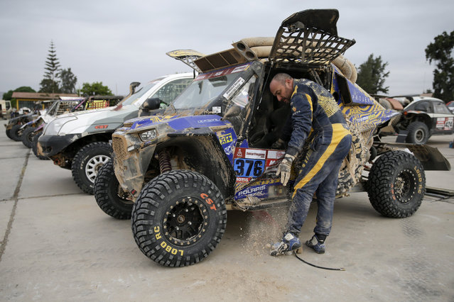 Driver Maciej Domzala, of Poland,removes sand from his vehicle before the start of stage five on January 11, 2019. (Photo by Ricardo Mazalan/AP Photo)