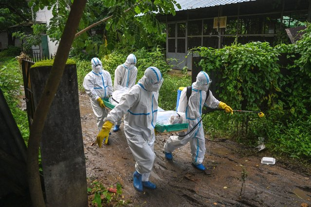 Volunteers wearing personal protective equipment (PPE) carry the body of a victim of the Covid-19 coronavirus to a cemetery in Hlegu Township in Yangon on July 10, 2021. (Photo by Ye Aung Thu/AFP Photo)
