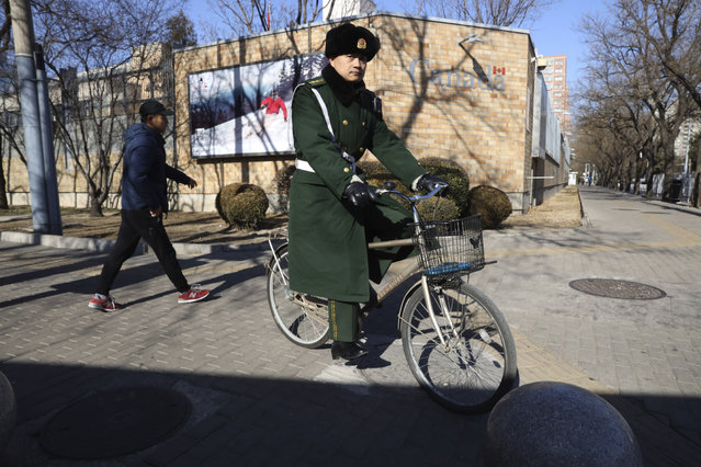 A Chinese paramilitary policeman rides past the Canadian embassy in Beijing, China, Wednesday, January 16, 2019. Chinese President Xi Jinping's government is sparing no expense to its international reputation in its determination to force Canada to back down over the case of a Chinese telecommunications executive it detained last month. (Photo by Ng Han Guan/AP Photo)